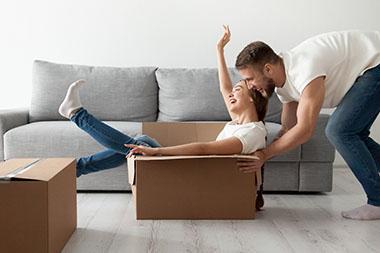man pushing woman in packing box