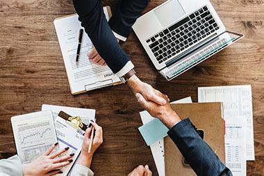 Investors shaking hands across desk