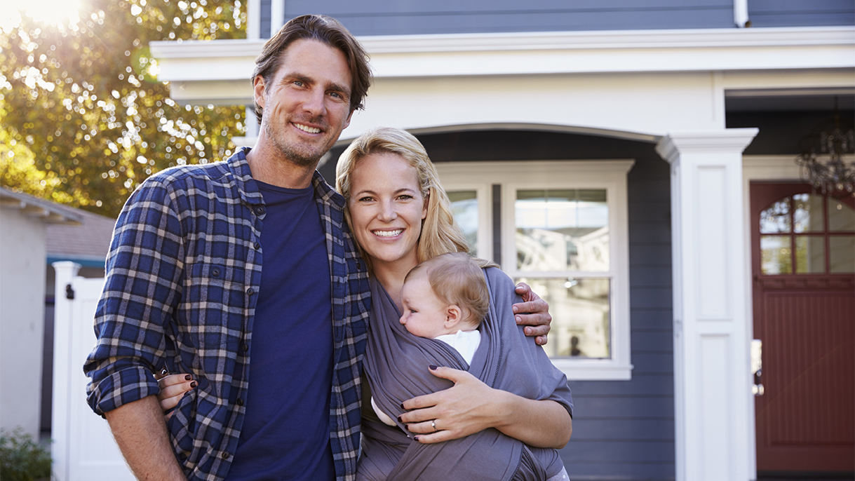 couple with baby standing in front of house